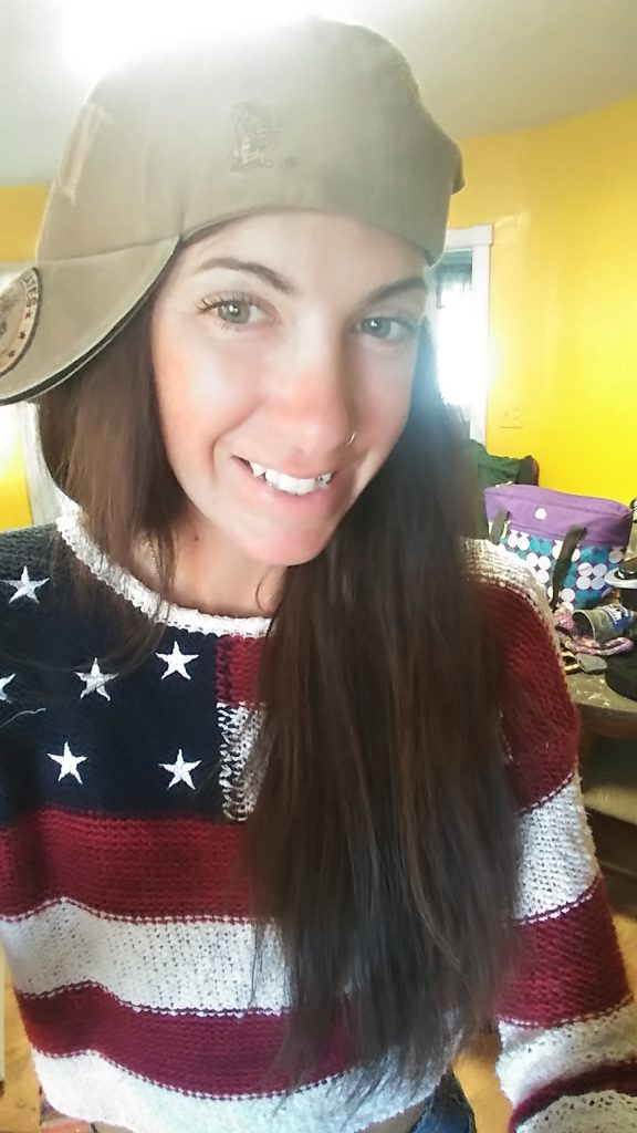 Ellison Hartley wearing an army hat and an American flag sweater smiling at the camera from inside her home