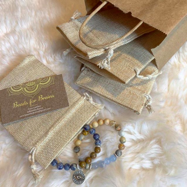 Packaging for the beaded bracelets including a paper bag, business card, and small hemp bags